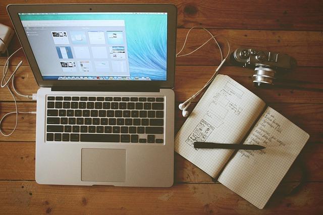 zápisník vedle laptopu a fotoaparátu