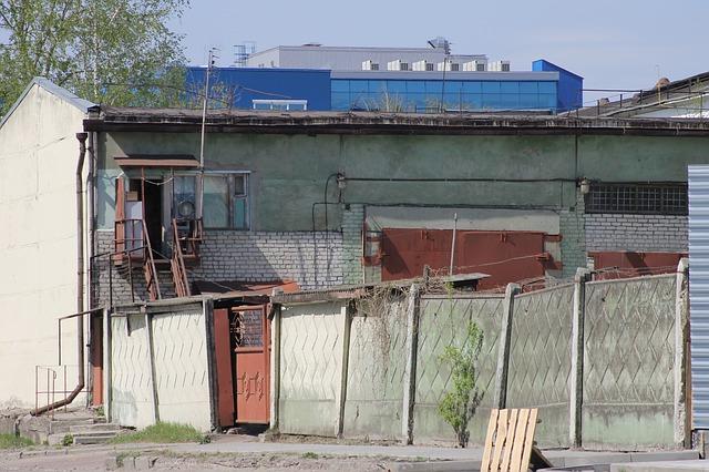 Starý betonový plot, v pozadí nevzhledná budova