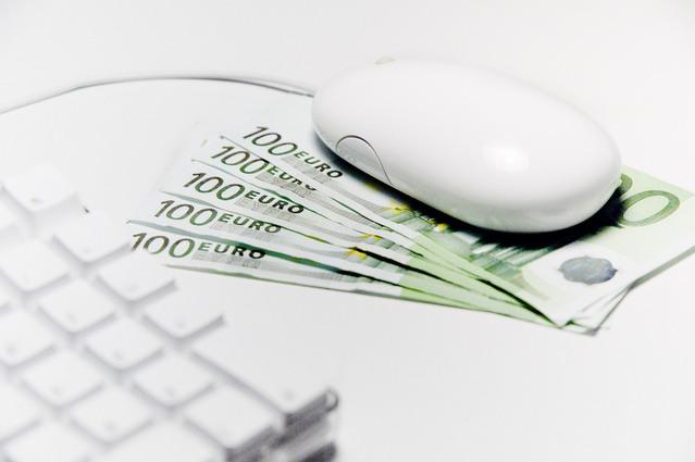 počítačová myš postavená na papírových bankovkách